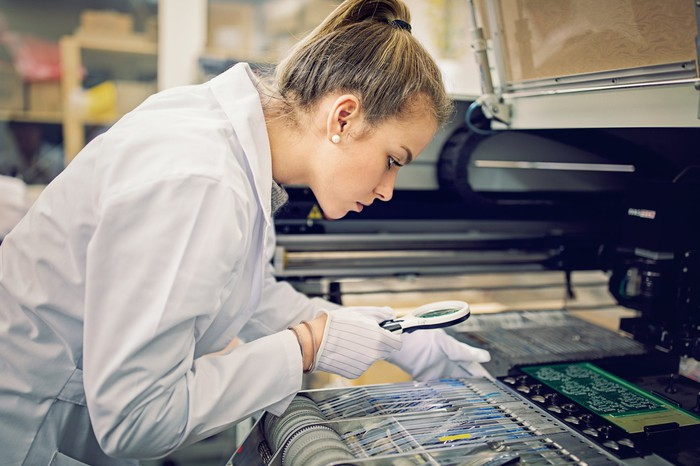 Person in lab coat examining semiconductor chips.