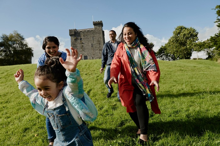 A family on the grass in front of a castle rented through Airbnb.