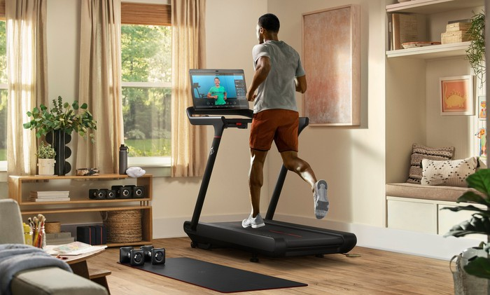 A Peloton user on a Tread+ connected fitness machine.