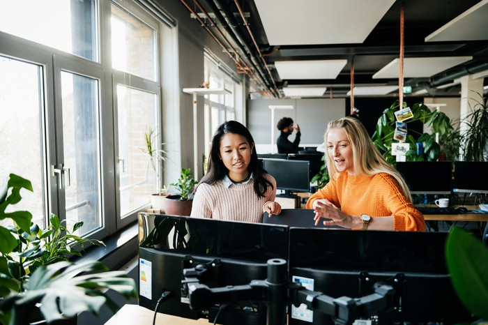 Two women sitting in front of computers in an office.