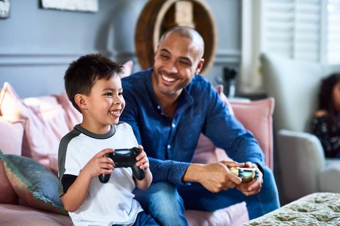 Un adulte et un enfant sourient en jouant à des jeux vidéo.