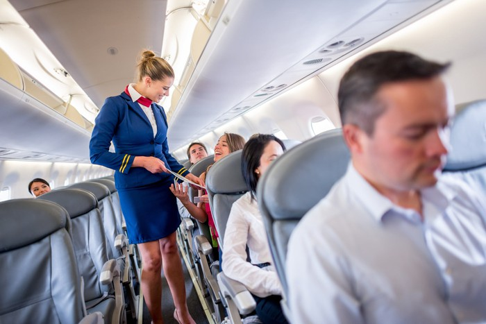 Smiling flight attendant talks to an airplane passenger while standing in the aisle.