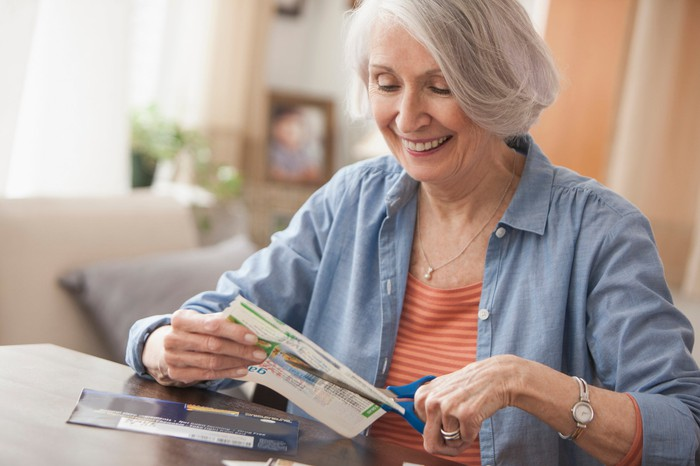 A woman clipping coupons and smiling.