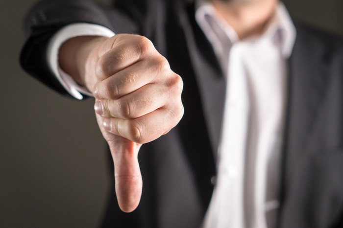 A person wearing a sportscoat giving a thumbs-down.
