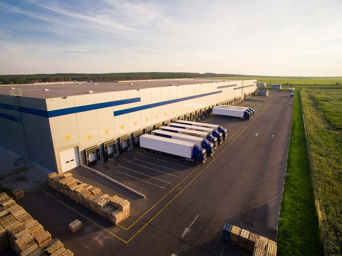 Picture of eight semi-trailer trucks parked outside of a logistics facility.