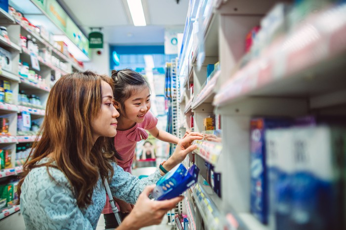 Adult and child looking at the shelves of a pharmacy.
