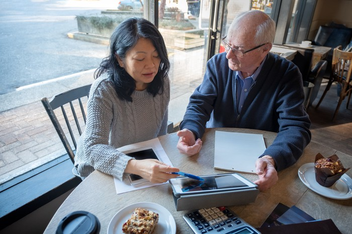 Two people working on their finances while eating breakfast.