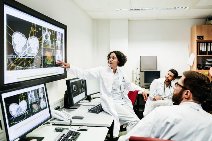 A clinician showing colleagues something displayed on a big screen.
