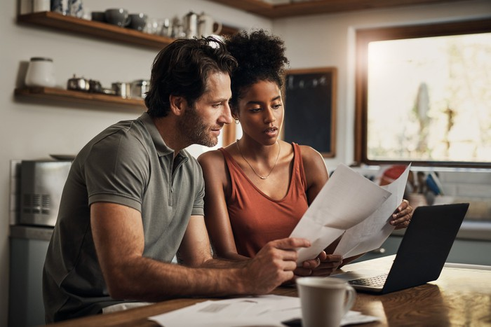 Two people looking at paperwork at kitchen table.