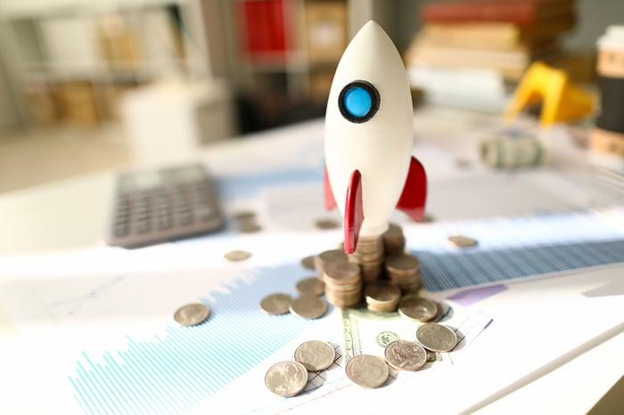 Une fusée-jouet placée au sommet d'un tas de pièces en désordre entouré de documents affichant des mesures financières.