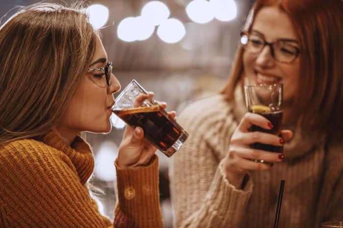 Deux personnes buvant du cola.