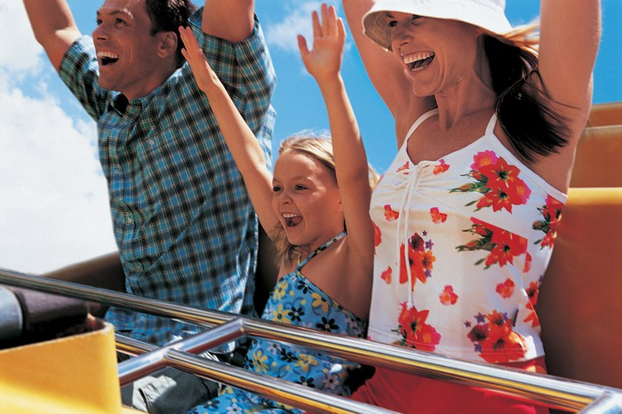 A family on a roller coaster with their arms in the air.
