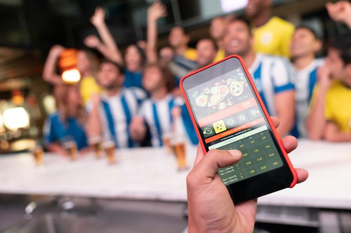 A cell phone showing a winning online bet with sports fans in the background.