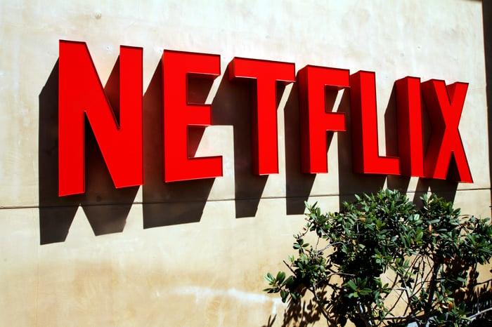 A red Netflix logo on a beige stucco wall.