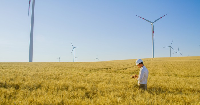 An engineer stands in a field with wind turbines in the background.