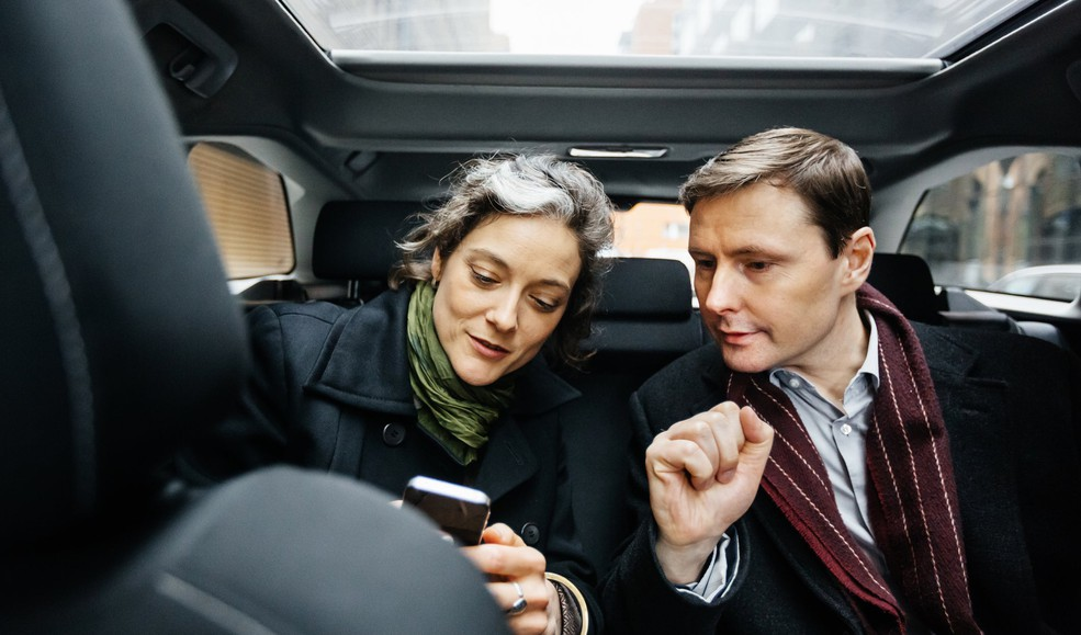 coworkers in back of car look at phone
