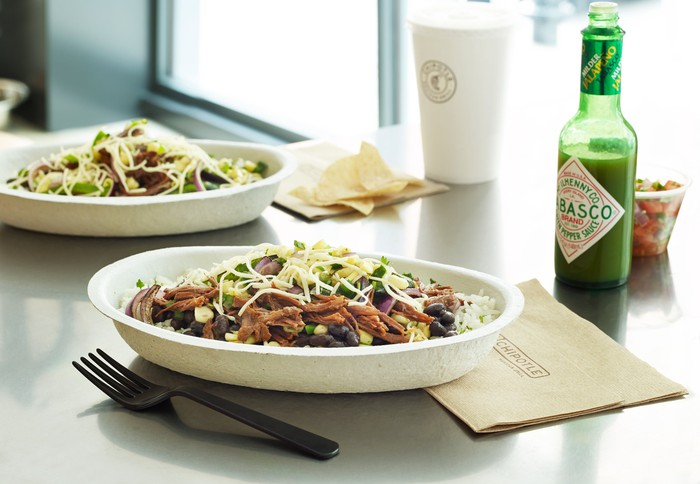 A Chipotle burrito bowl on a table next to a fork, a napkin, and a bottle of Tabasco sauce.
