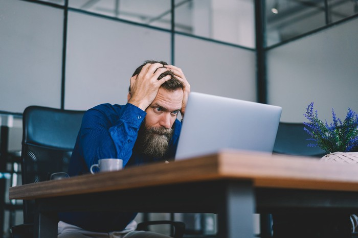 A person staring at a laptop holding their head in their hands.