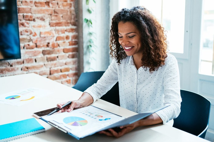 A person smiles at a folder containing graphs and charts.