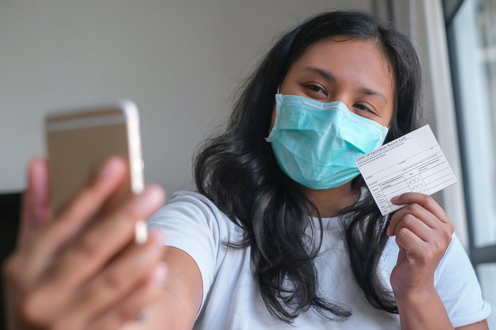 A person takes a selfie with a vaccination card post vaccination.