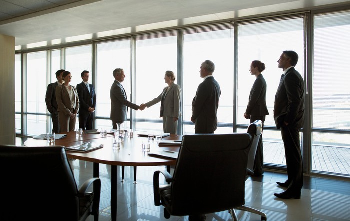 People standing around two other people shaking hands in conference room.