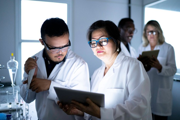 Two researchers work together in a lab, faces lit by a tablet, with others in the background.