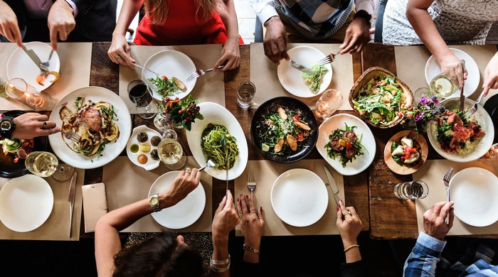Overhead view of eight people at a table with food.