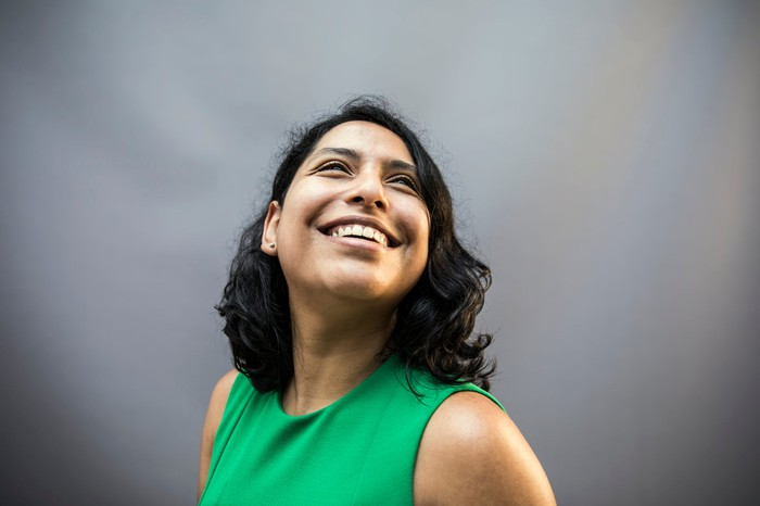 happy person smiling against gray background