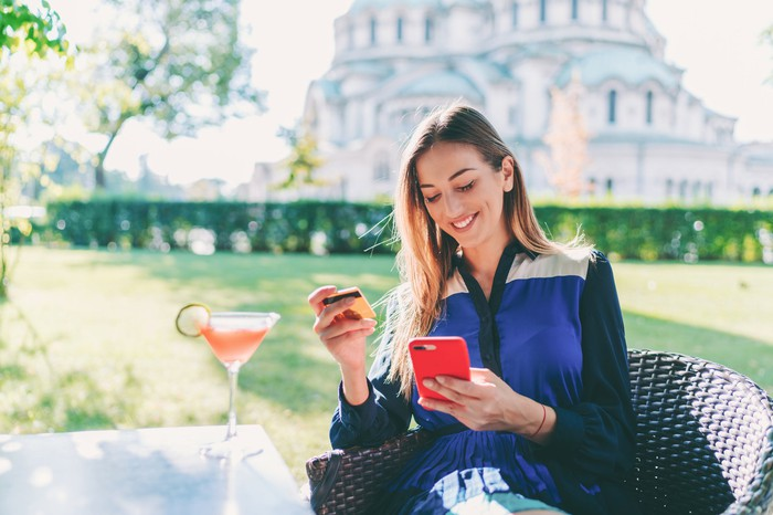 A smartphone user enters credit card information into an app while sipping a cocktail.