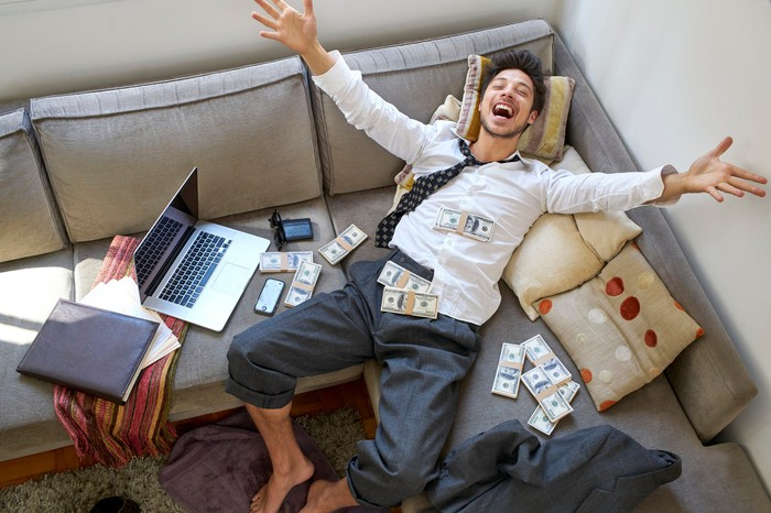 Disheveled person with hands up in the air, laying on couch next to a computer. Stacks of money are scattered around.