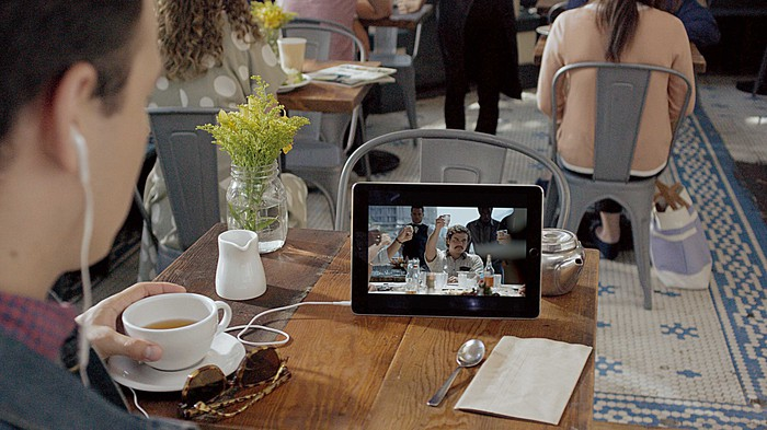 a person sitting at a table holds a coffee cup while viewing a video on a tablet computer resting on the table in what appears to be a coffee house