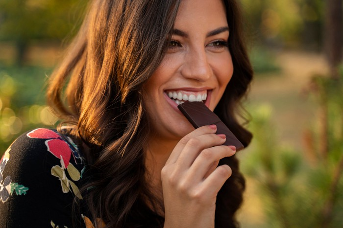 A person enjoying a piece of chocolate outside.