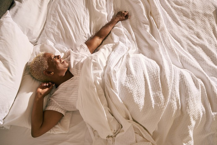 Person waking up and stretching in comfortable bed.