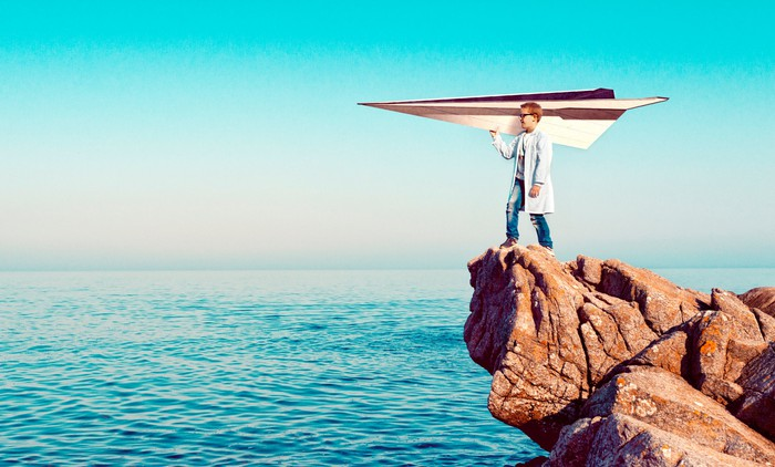 Kid in lab coat stands on a cliff holding a large paper airplane
