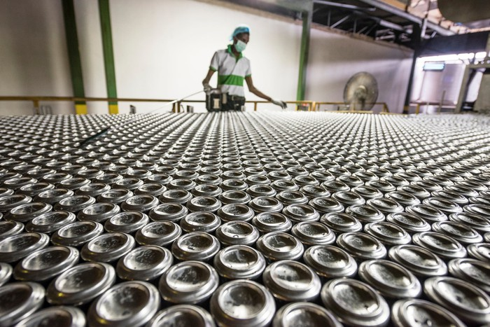 A person working in an aluminum beverage can packaging facility.