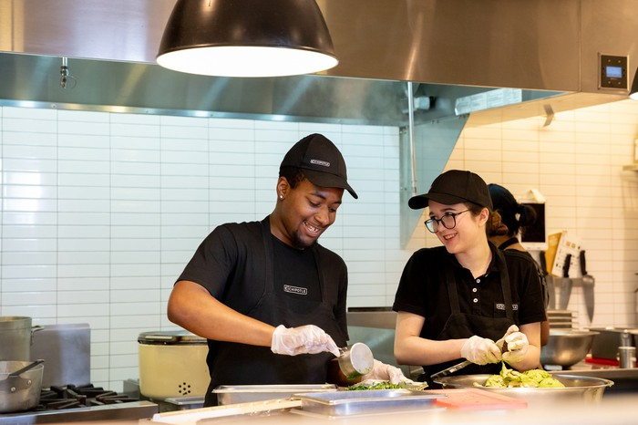 Two smiling Chipotle workers preparing food.