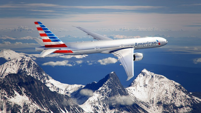 An American Airlines plane in flight, with snow-capped mountains in the background.