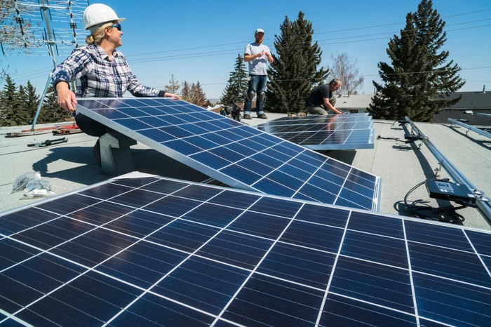 Workers install solar panels on a rooftop.