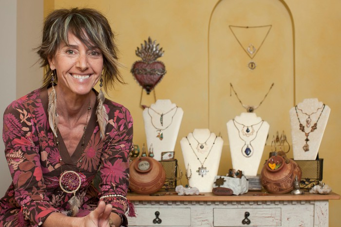 A middle aged woman smiles outside her jewelry display booth.