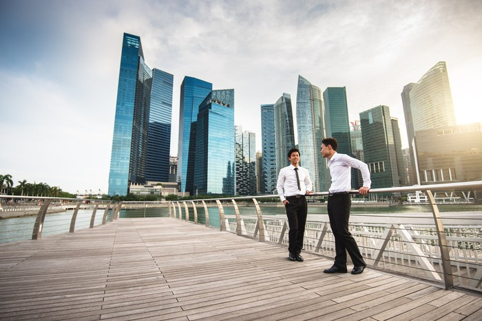 Two businessmen stand before the Singapore skyline.