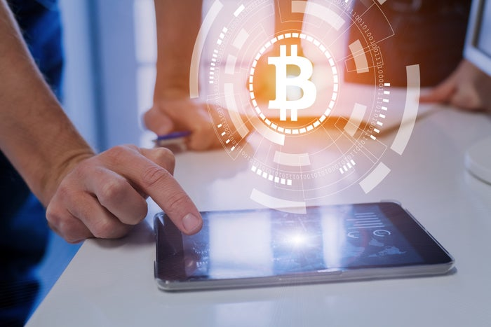 A hand touches a tablet with a bitcoin symbol superimposed over the image.