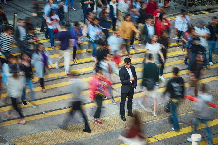 A smartphone user stands in the middle of a crowded pedestrian crossing.