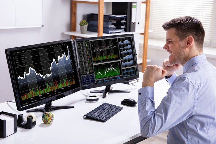 A person looking excitedly at stock price charts on computer.