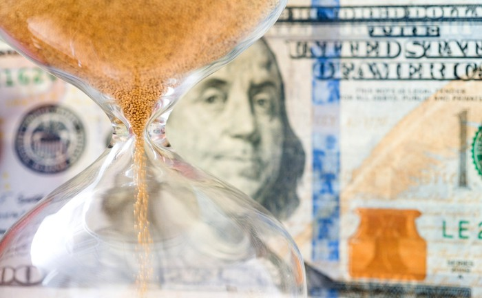 An hourglass in front of a hundred-dollar bill.