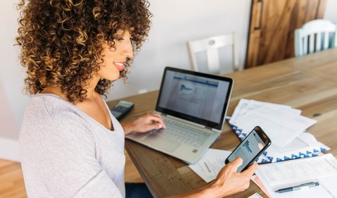 A person doing finances at home on a smart phone and laptop