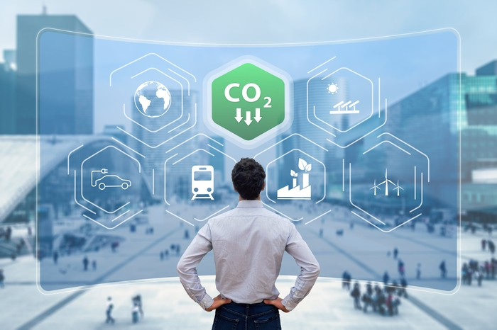 A person looking at a city street, with icons representing falling carbon dioxide emissions overlaid on top.