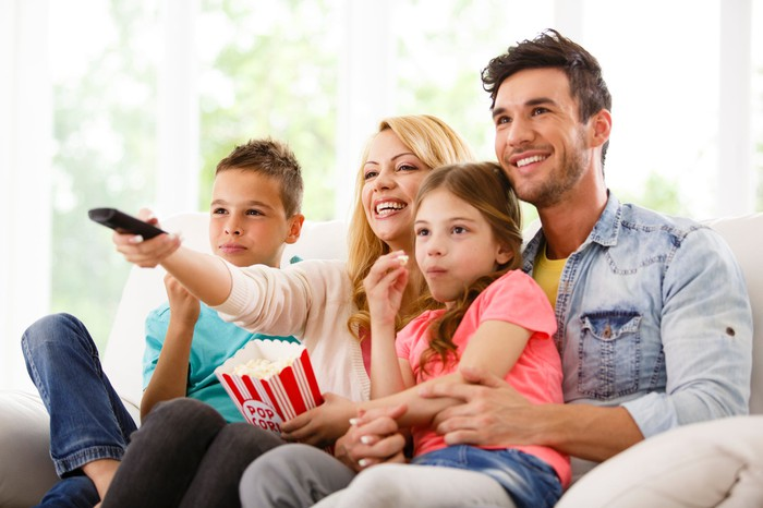 A smiling family watching a movie and eating popcorn at home.