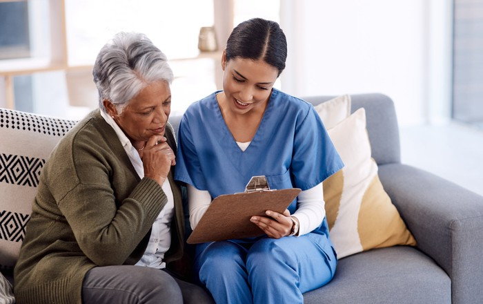 A nurse sitting on a sofa with a patient helping fill out paperwork.