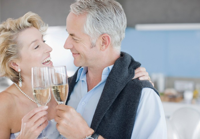 an elderly couple clinking champagne glasses