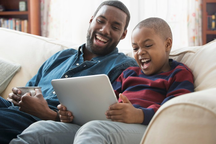A child and adult laughing while looking at a tablet.